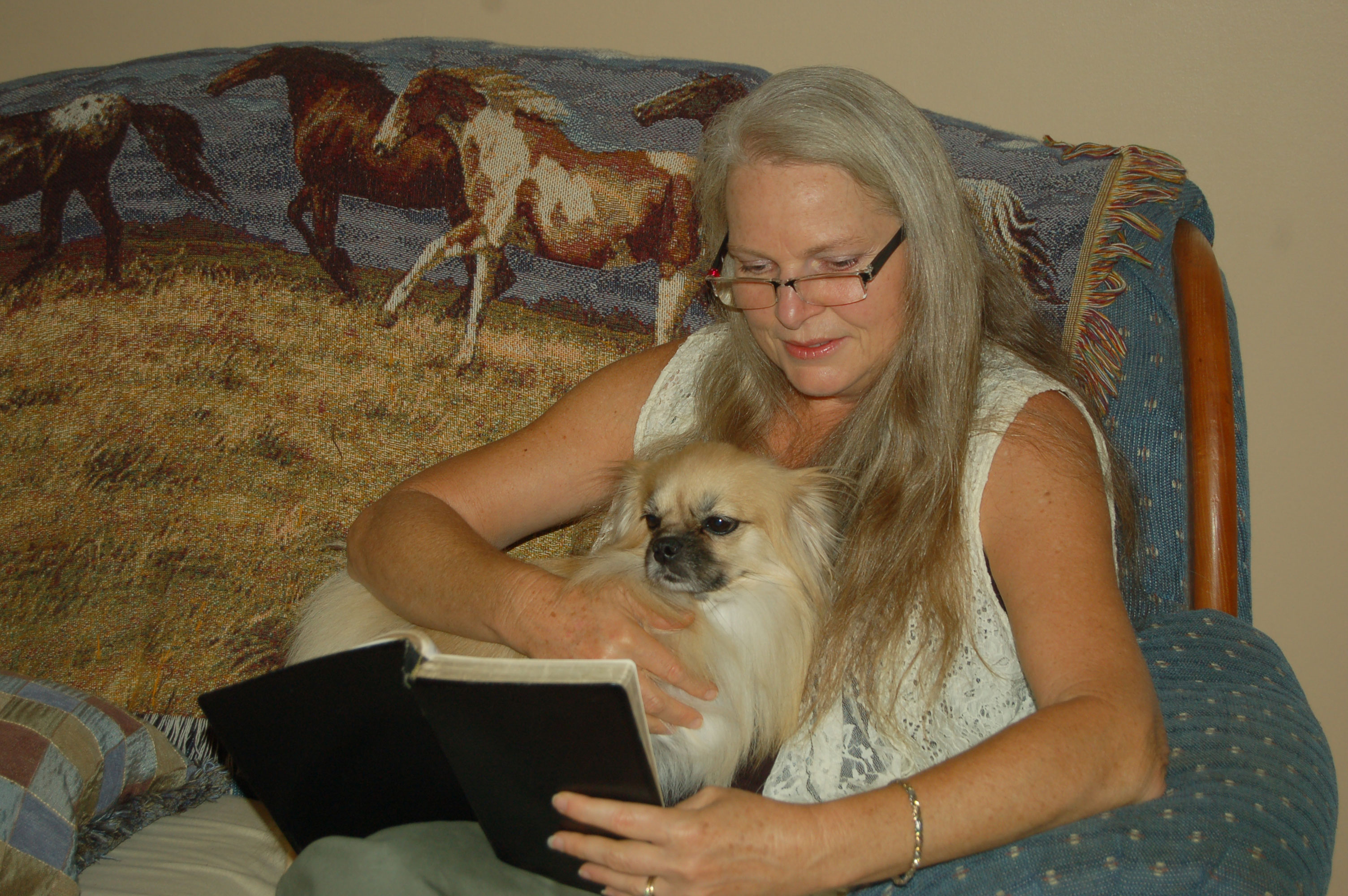 Christian Stock Photos by Linda Bateman - Woman Reading Bible while Sitting on Sofa, with Dog
